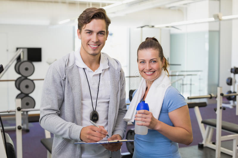 Personal trainer and client smiling at camera royalty free stock photos