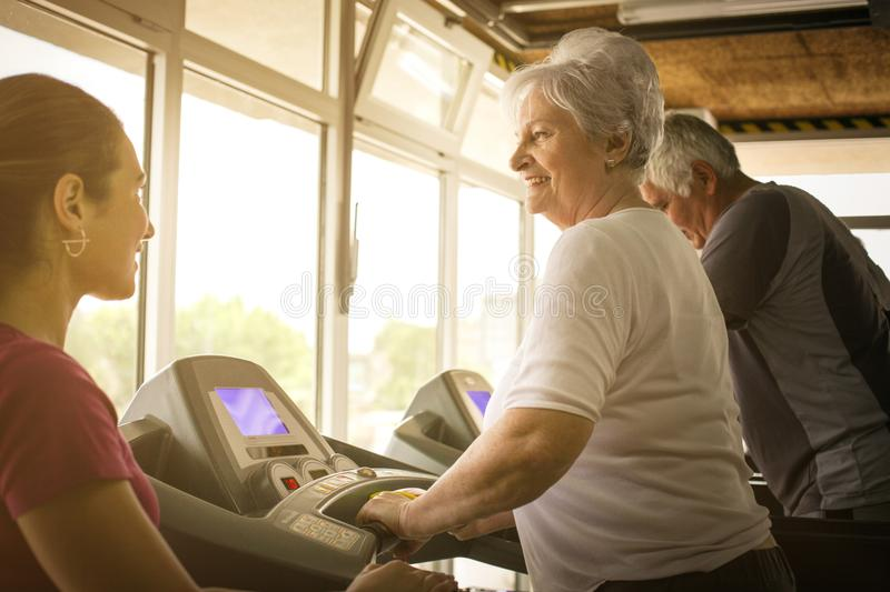 Personal trainer exercise helps elderly couple. royalty free stock image