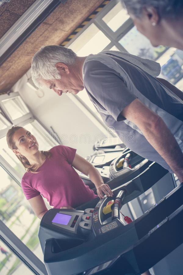 Personal trainer exercise helps elderly couple. stock image