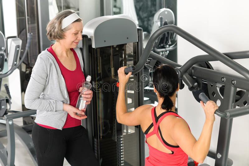 Personal trainer at fitness center show exercise royalty free stock photography