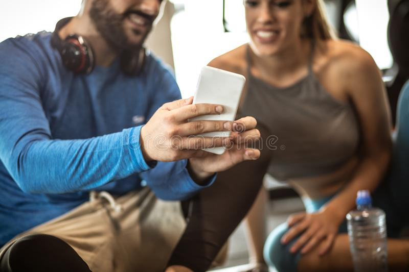 Personal trainer with girl sitting on floor and having conversation after exercise. stock images