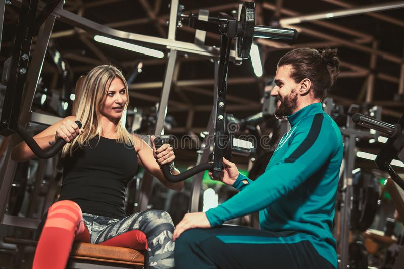 Personal trainer giving weightlifting training to girl. In gym royalty free stock image