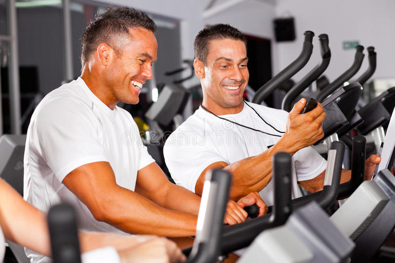 Personal trainer in gym. Fitness men and personal trainer in gym stock images