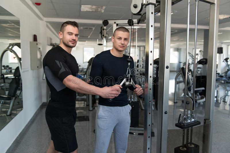Personal Trainer Helping Client In Gym. Personal Trainer Showing Young Man How To Train Triceps On Machine In The Gym stock image