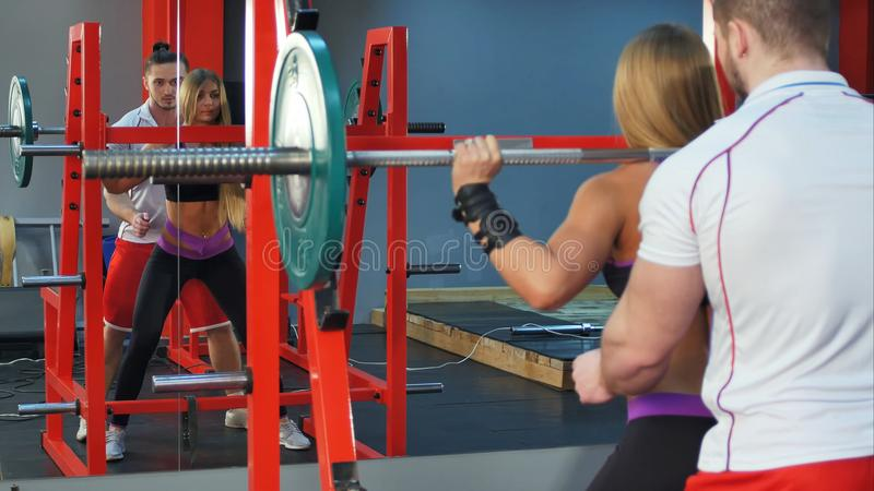 Personal trainer helping female client lifting barbell at the gym royalty free stock photos