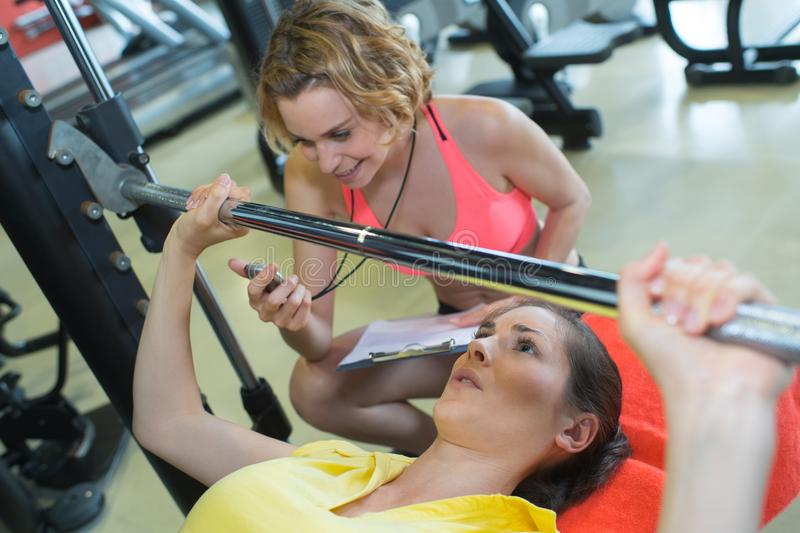 Personal trainer helping woman for correct bench press-training. Personal trainer helping women for correct bench press-training female royalty free stock image