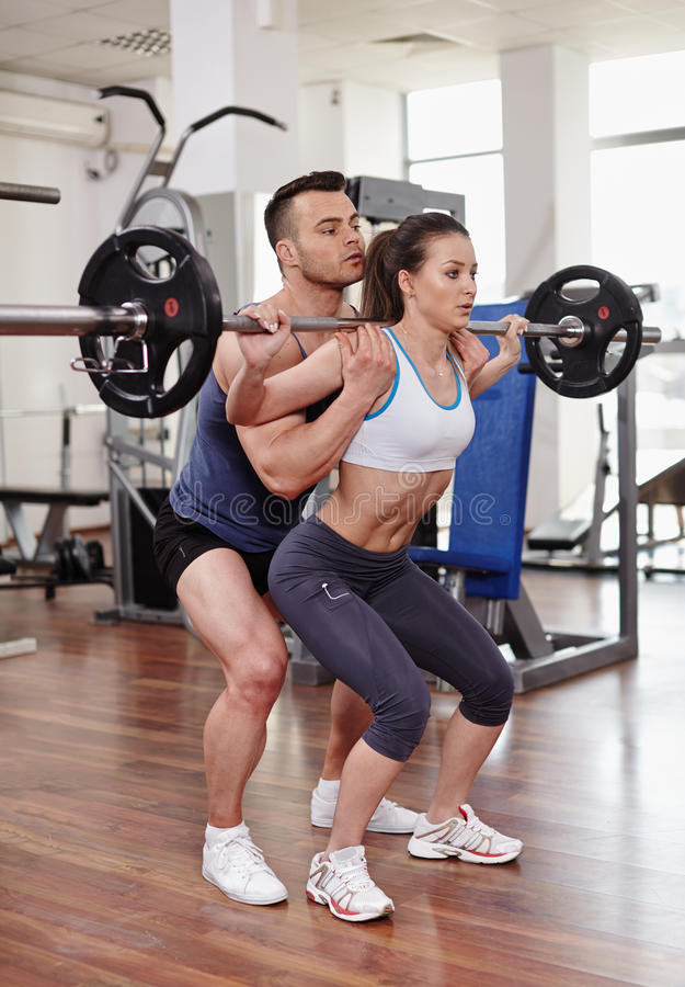 Personal Trainer Helping Woman At Gym Stock Photo