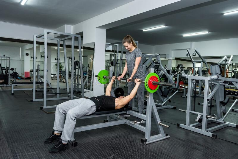 Personal trainer helping work with barbell in gym.  royalty free stock photos