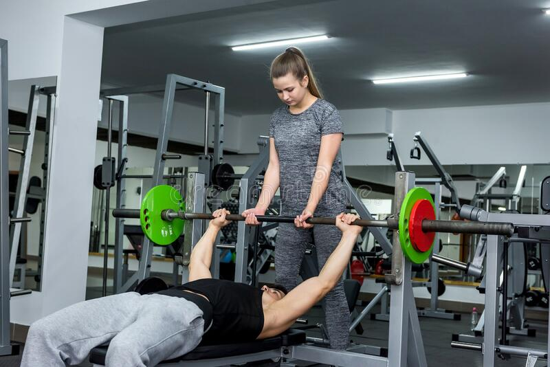 Personal trainer helping work with barbell in gym.  stock images