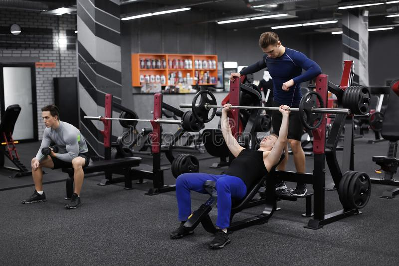 Personal trainer helping young man who is working out in gym royalty free stock photo