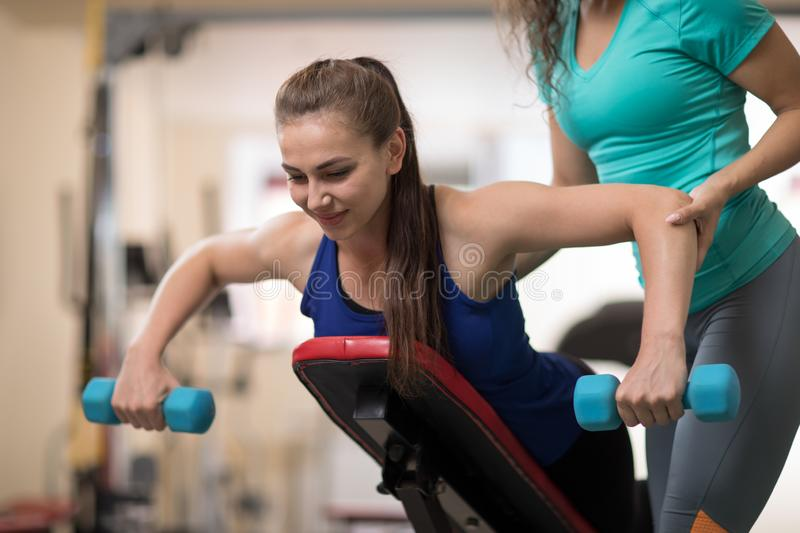 Personal trainer helping young woman with weight training equipment in gym royalty free stock image