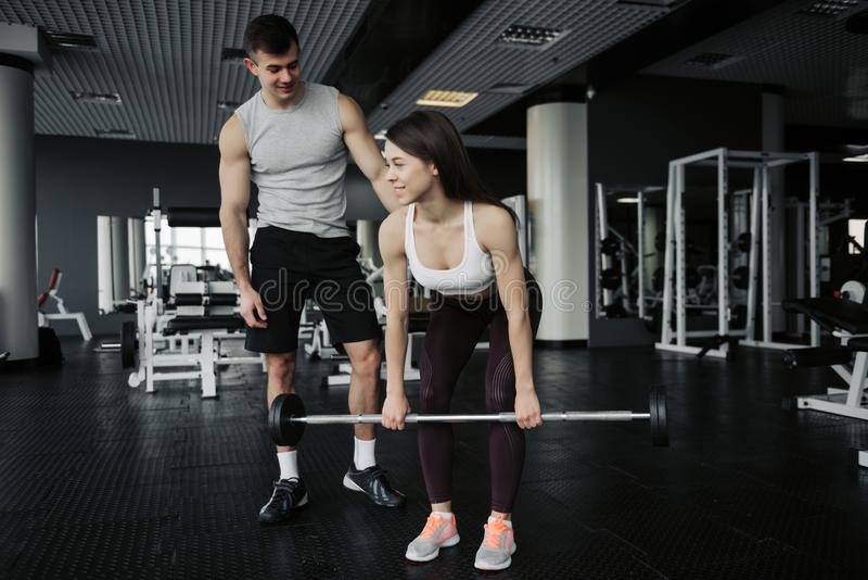 Personal trainer helping a young woman squats with dumbells in a gym. Personal trainer helping a young women squats with dumbells in a gym stock photography
