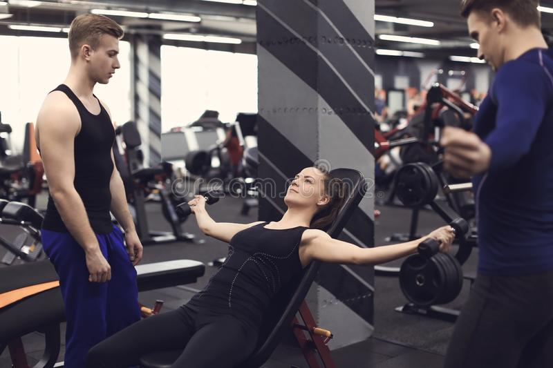 Personal trainer helping young woman to do exercises with dumbbells in gym stock images