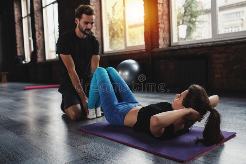 Personal trainer helps a girl with the gym exercises stock images