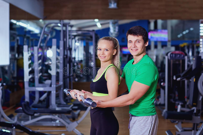 Personal trainer helps a girl lifting weights in the gym stock image
