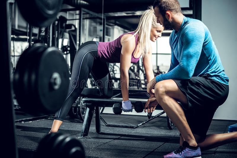 Personal trainer helps his client during row exercise. stock photography