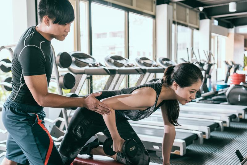 Trainer helps client do one-arm dumbbell row royalty free stock images