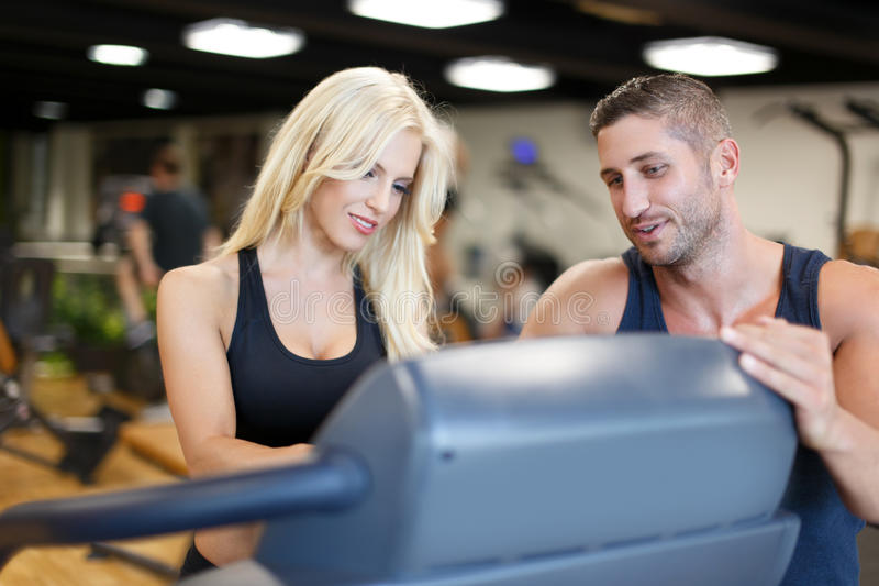 Personal trainer helps to blonde woman in gym royalty free stock photography