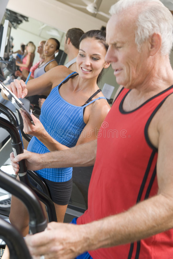 Personal Trainer Instructing Man On Treadmill Stock Image