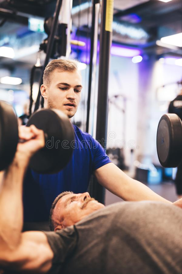 Personal trainer instructing older man during exercise. stock image