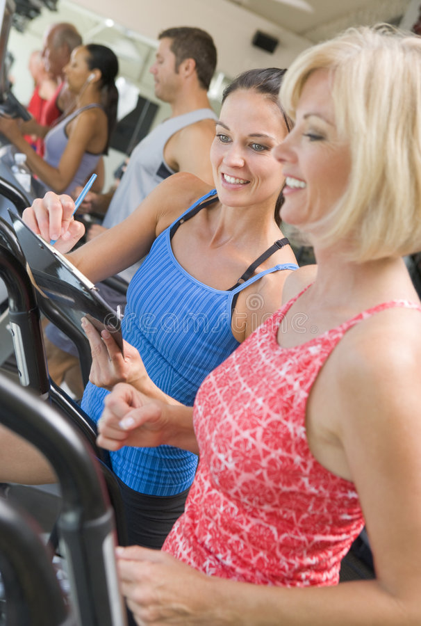 Personal Trainer Instructing Woman On Treadmill royalty free stock image