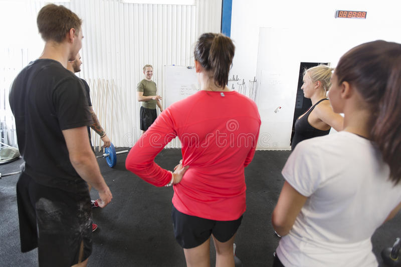 Personal trainer instructs his fitness workout team royalty free stock photo