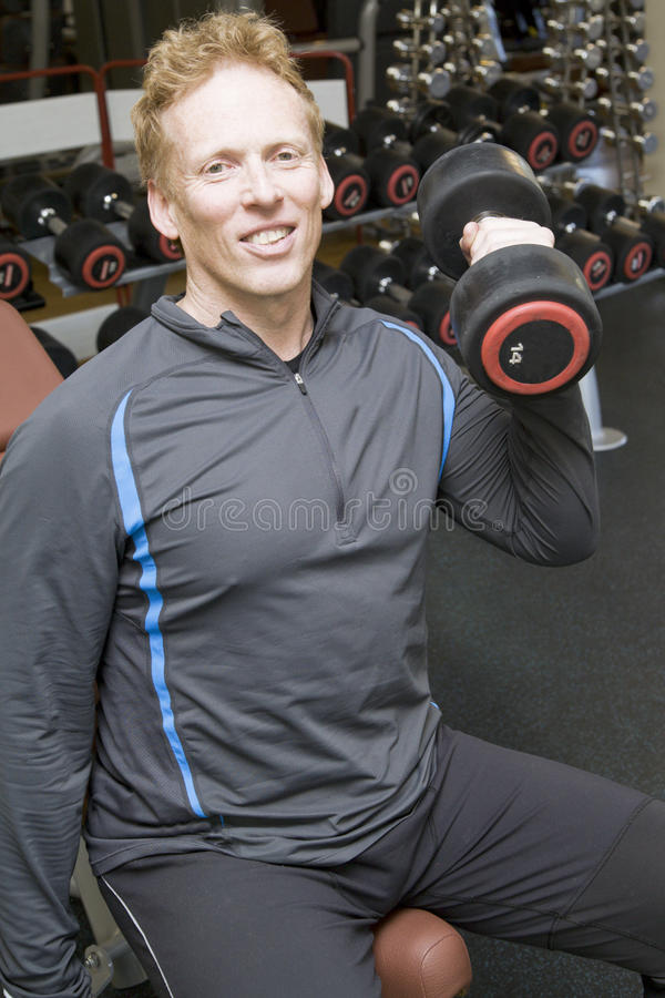 Personal Trainer Lifting Weights In A Modern Gym Stock Image