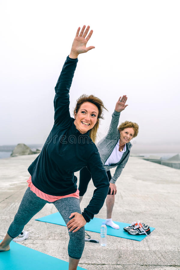 Personal trainer with senior woman with stretching side stock photography