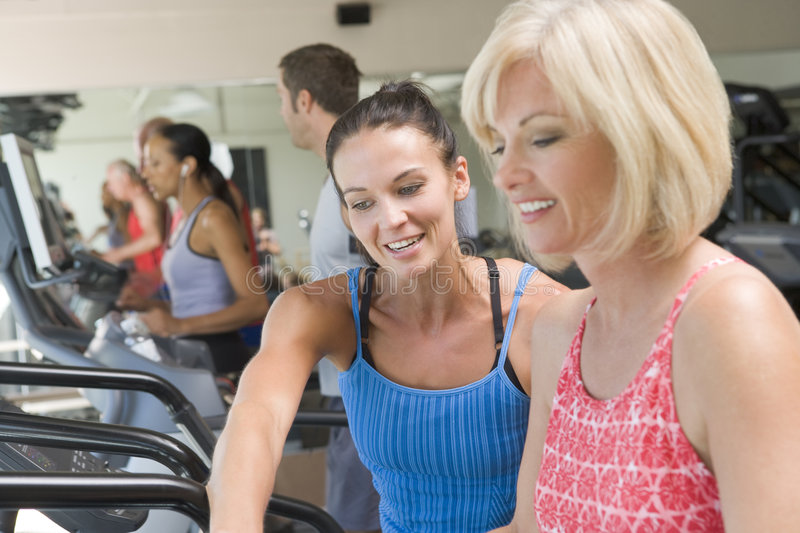 Personal Trainer Showing Woman On Treadmill royalty free stock photography