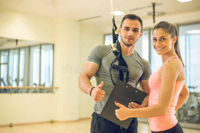 Personal trainer with suspension showing results to client. stock images