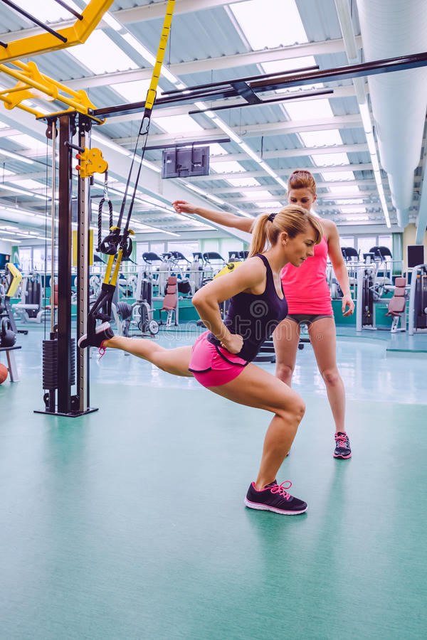 Personal trainer teaching to woman in suspension royalty free stock image