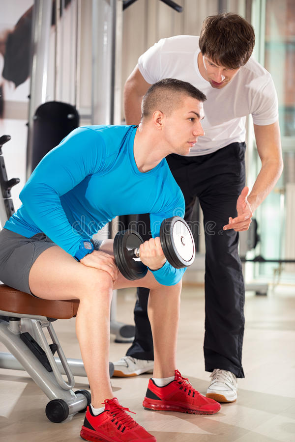 Personal trainer on training with client. Personal trainer on weights lifting training with client royalty free stock image