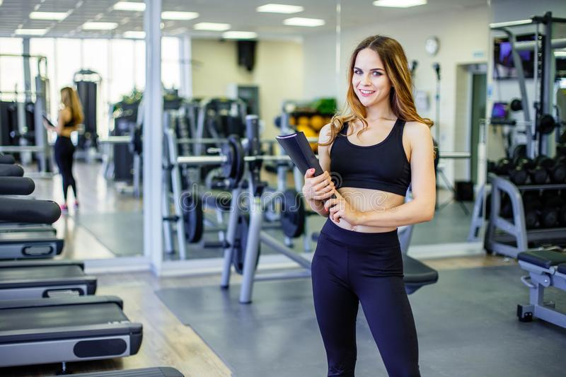 Personal trainer woman holding clipboard with training plan in gym. stock photo