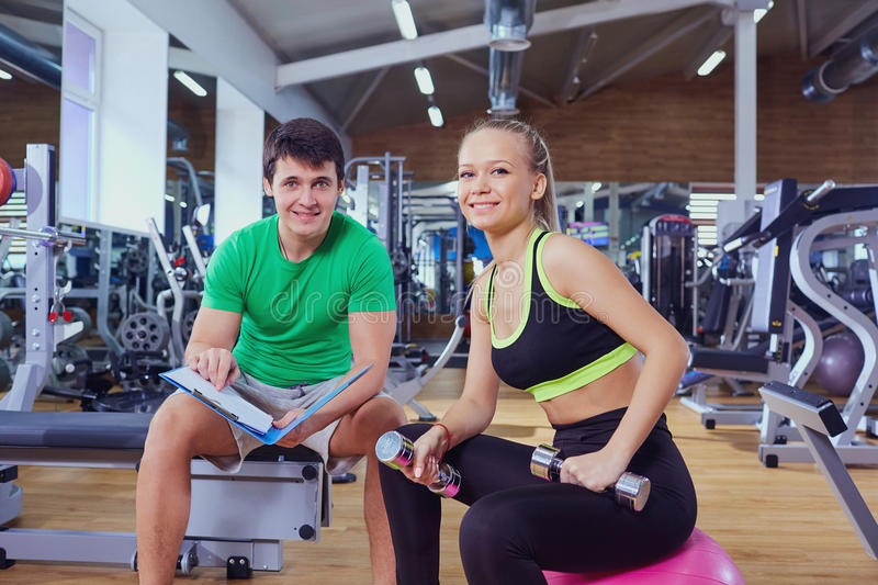 Personal trainer and a woman relaxing in the gym after exercise stock photography