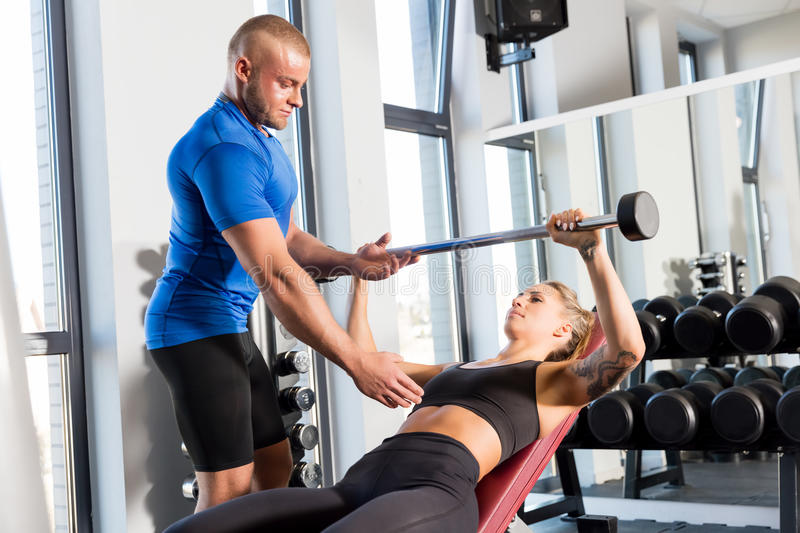 Personal trainer working with a client at the gym. stock photography