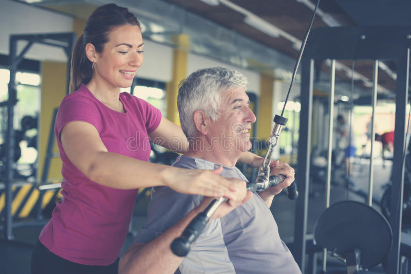 Personal trainer working exercise with senior man. royalty free stock photos
