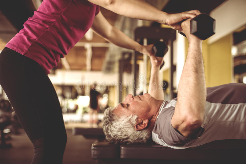 Personal trainer working exercise with senior man. stock photos