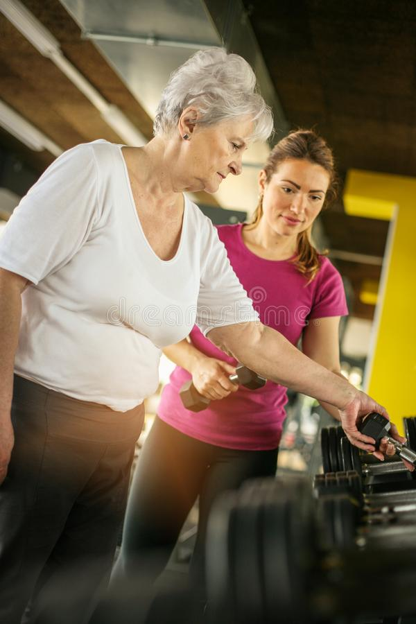 Personal trainer working exercise with senior woman in the gym. stock image