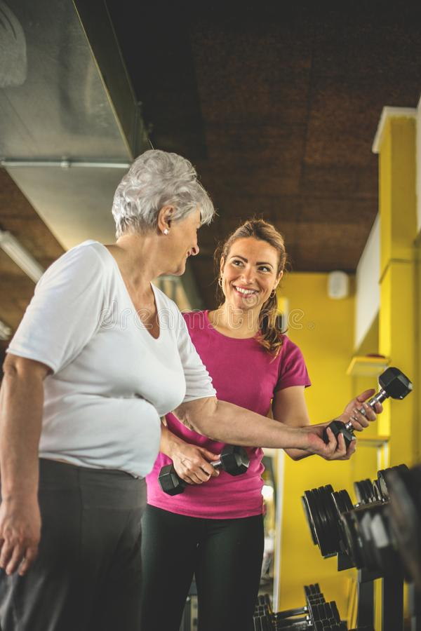 Personal trainer working exercise with senior woman in the gym. royalty free stock images