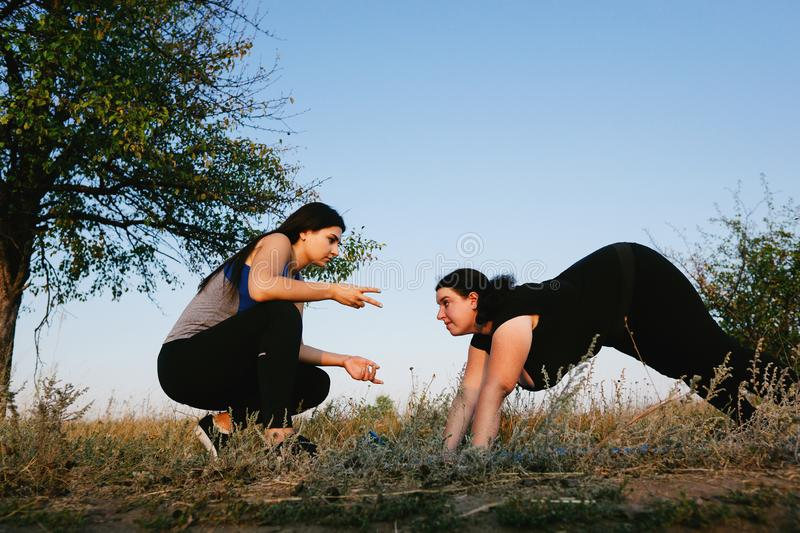 Personal trainer working with her client outdoors. Overweight women doing pushups on mat with assistance of her fitness instructor support. Sport, training stock photography
