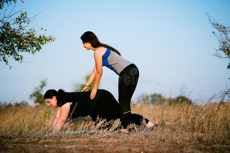 Personal trainer working with her client outdoors. Overweight women doing pushups on mat with assistance of her fitness instructor support. Sport, training stock images