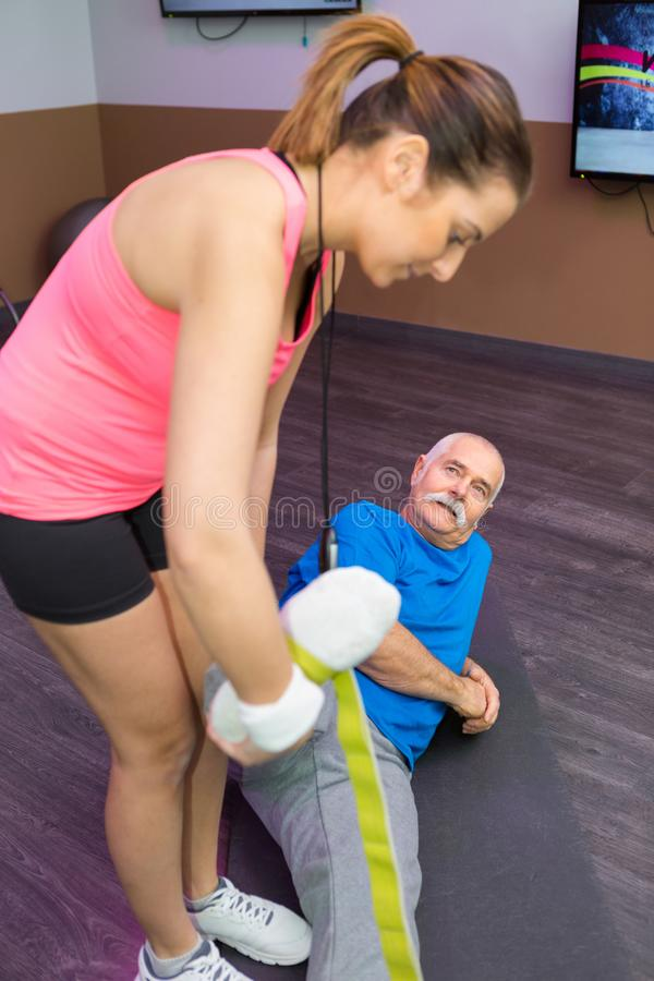 Personal trainer working with senior man using strap royalty free stock photo