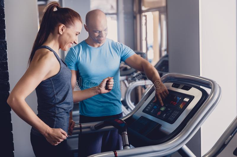 Personal training with a trainer on a treadmill. The trainer controls the correctness of the exercise when using a treadmill for cardio. Control coach in the stock photo