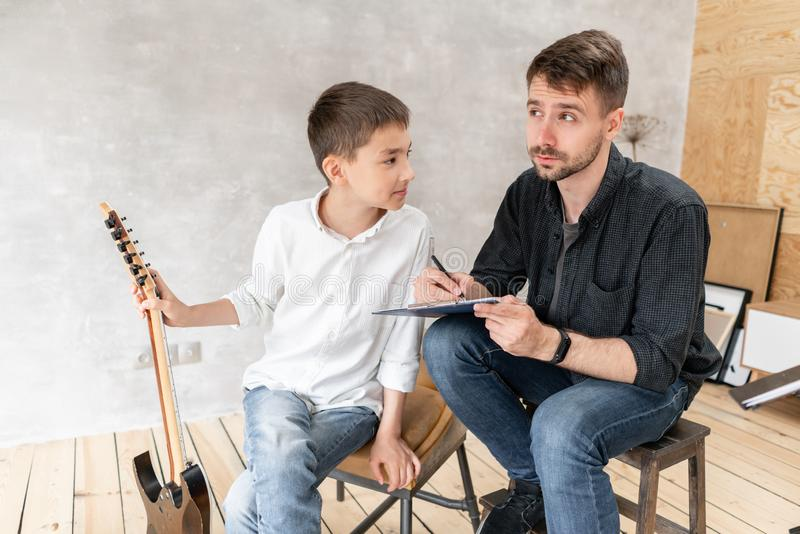 A personal tutor writes notes on music sheet for his student and explain how to play them. stock photo