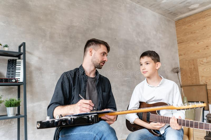 A personal tutor writes notes on music sheet for his student and explain how to play them. royalty free stock photography