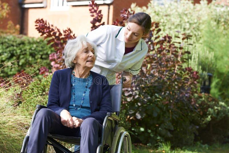 Personale che dispensa le cure che spinge donna maggiore in sedia a rotelle immagini stock libere da diritti