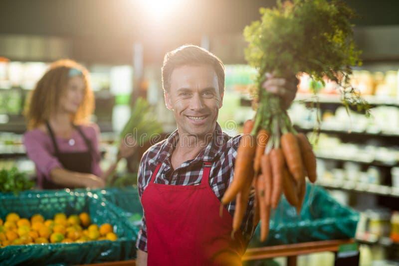 Personale maschile sorridente che tiene mazzo di carote nella sezione organica fotografia stock libera da diritti
