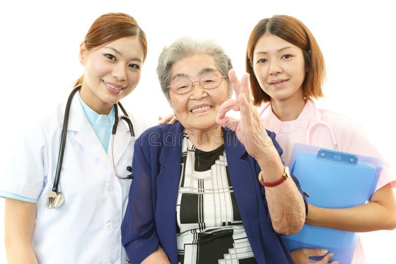 Personale medico sorridente con la donna anziana fotografia stock