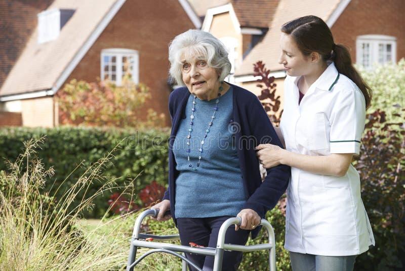Personale sanitario che aiuta uomo senior a camminare in giardino facendo uso della struttura di camminata immagine stock libera da diritti