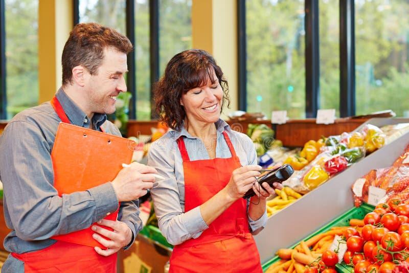 Personale in supermercato facendo uso del cellulare fotografia stock